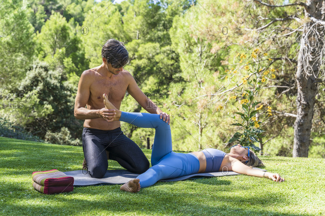 Shirtless male massage therapist treating female tourist's leg at spa during sunny day