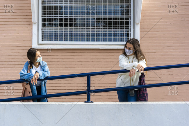 Female teenage friends looking at each other while leaning on railing during covid-19