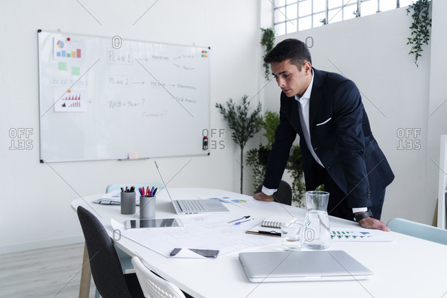 Handsome male professional leaning on desk while planning strategy at creative office