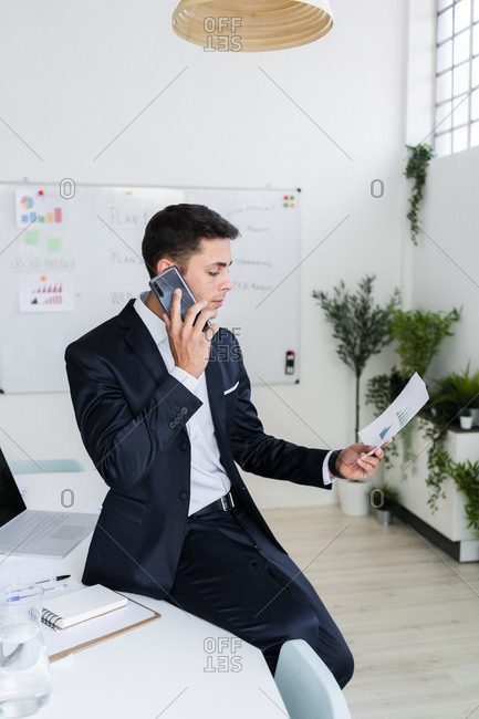 Young male professional talking on phone while looking at document in creative office