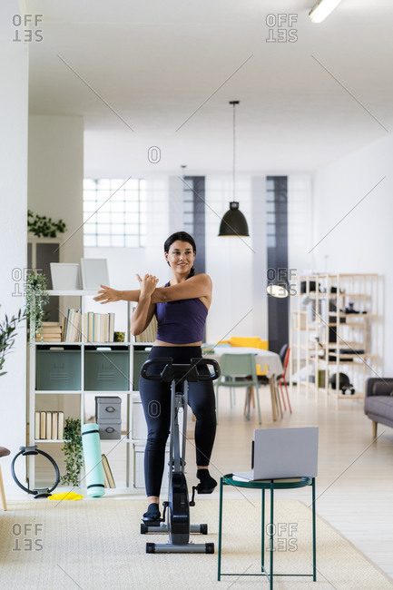 Young female athlete doing stretching exercise while sitting on exercise bike at home