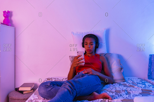 Teenage girl lying on bed using smart phone to listen music through headphone at home