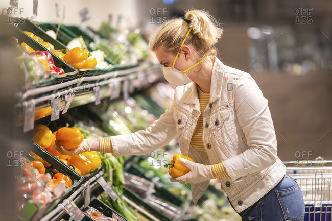 Teenage girl wearing protective mask and gloves choosing bell peppers at supermarket