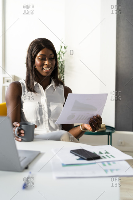 Smiling businesswoman with coffee cup reading paper while sitting on chair at office