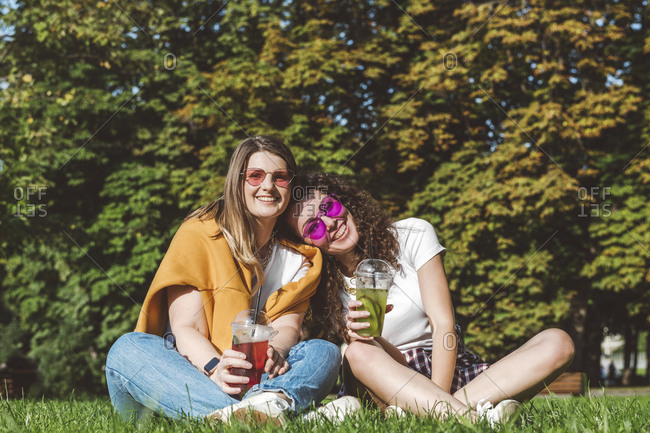 Smiling female friends sitting with fresh lemonade on grass at park during sunny day