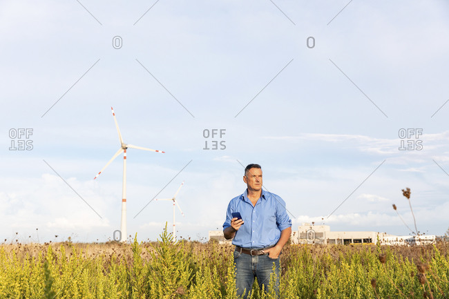 Mature businessman holding smart phone while standing against wind turbines on field