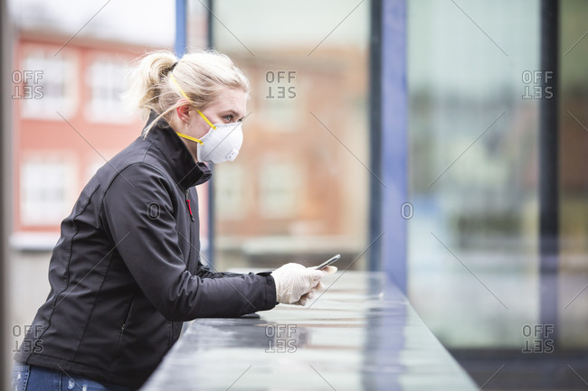 Blond teenage girl with smartphone wearing protective mask and gloves using outdoors
