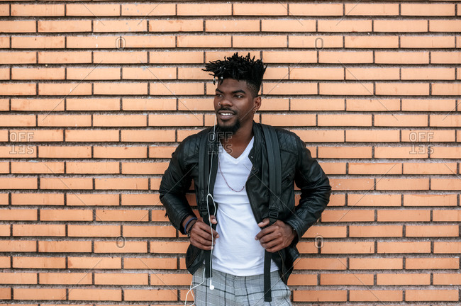 African man wearing leather jacket listening music while standing against brick wall