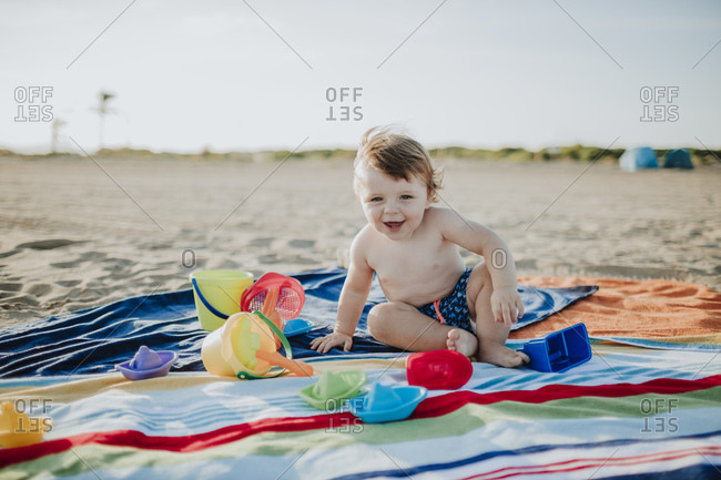 Cute little baby boy playing while sitting on colorful towel at beach during sunset