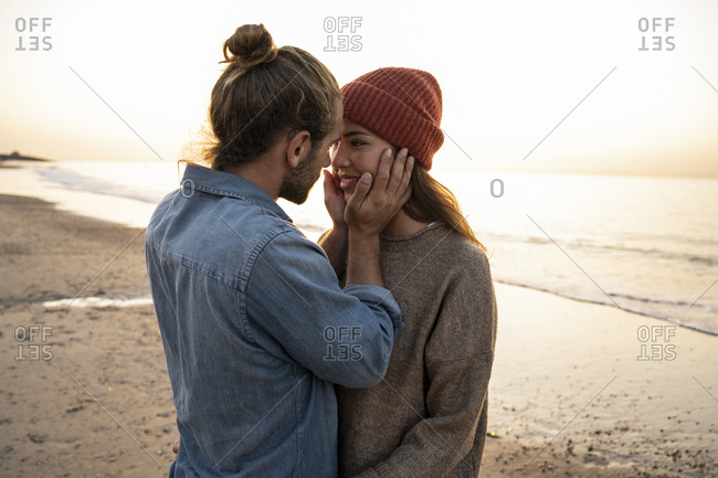 Romantic young man touching girlfriend's face while standing at beach during sunset
