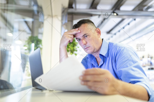 Overworked businessman staring at document while sitting with laptop in coffee shop