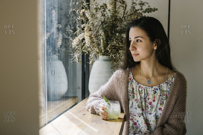 Young woman with lemonade glass looking through window while sitting at coffee shop