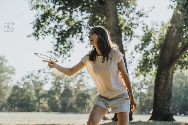 Happy mature woman throwing frisbee ring while standing in public park on sunny day