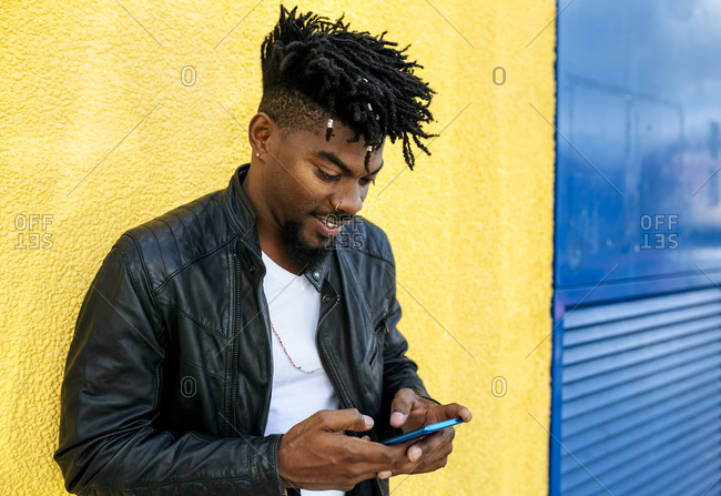Close-up of mid adult man with locs using mobile phone while standing against wall