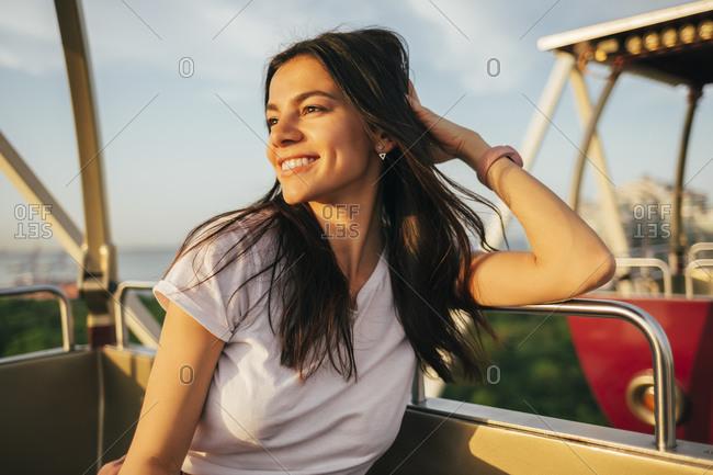 Smiling beautiful young woman looking away while enjoying sunset from Ferris wheel