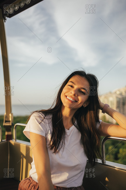 Smiling beautiful young woman sitting with hand in hair enjoying Ferris wheel ride