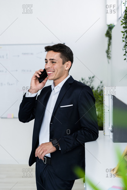 Smiling businessman talking on phone while standing by cabinet at creative office