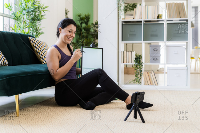 Female influencer showing graphics tablet while video recording on camera at home