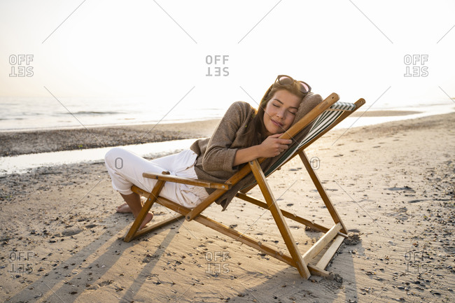 Relaxed woman reclining on folding chair at beach against clear sky during sunset