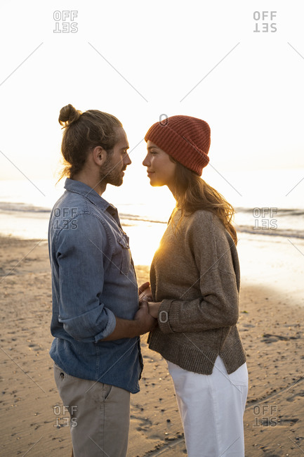 Romantic young couple looking at each other while standing on shore during sunset