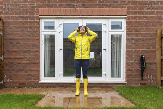 Woman wearing raincoat looking up while standing in back yard during rainy season