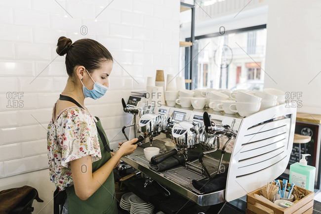Young woman with face mask making coffee while standing in kitchen at coffee shop