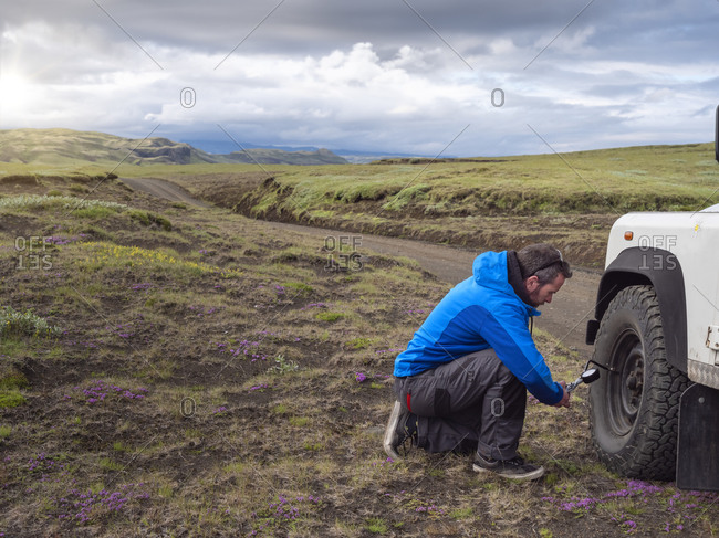 Male tourist kneeling while examining tire pressure through equipment at roadside