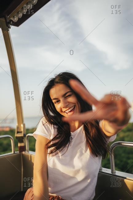 Smiling beautiful young woman showing peace sign while enjoying Ferris wheel ride