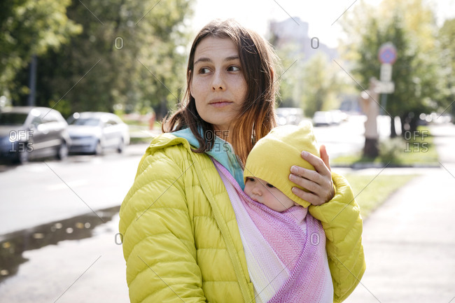 Mother holding baby wrapped in blanket while standing on street during sunny day
