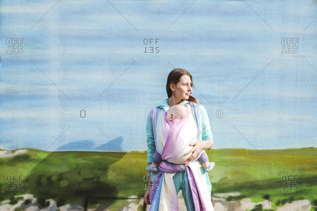 Mother carrying baby wrapped in blanket looking away while standing against wall
