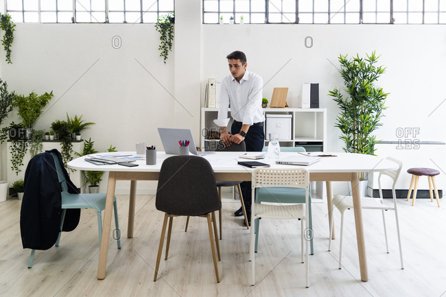 Businessman looking at laptop on desk while planning strategy in creative office