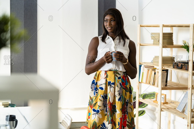 Businesswoman with coffee cup looking away while standing by bookshelf at office