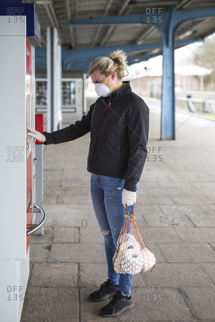 Teenage girl wearing protective mask and gloves using ticket machine at platform