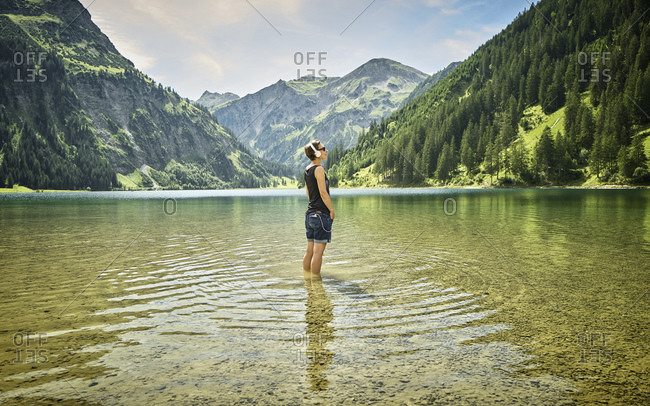 Mature woman standing knee deep in Vilsalpsee while listening music on sunny day