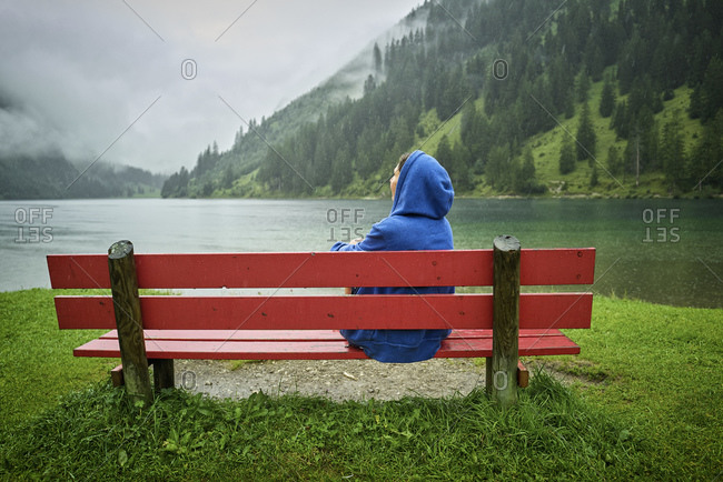 Woman wearing blue hood sitting on bench at lakeshore while looking at mountains