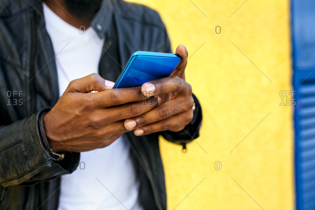 Close-up of mid adult man wearing leather jacket using mobile phone against wall