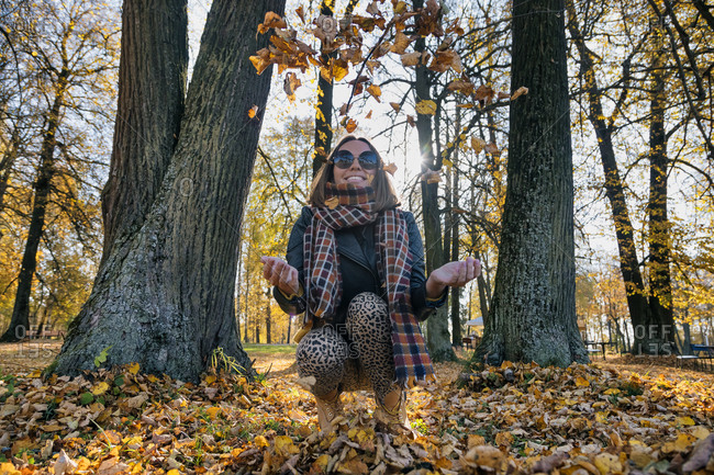 Cheerful woman throwing dry autumn leaves while crouching against trees at park