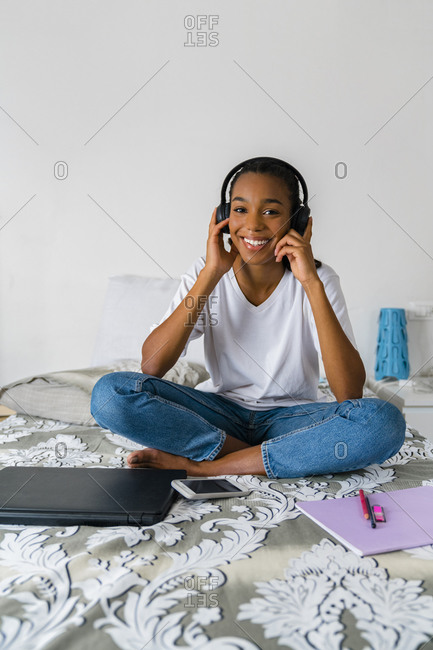 Smiling teenage girl with cross legged listening to music while sitting at home