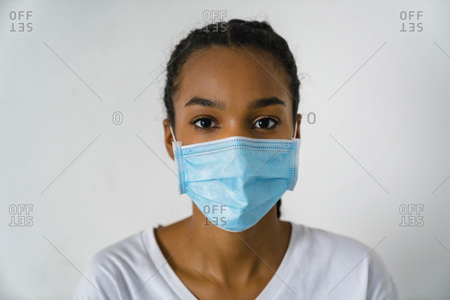 Teenage girl wearing protective face mask standing against wall during covid-19