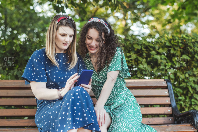 Smiling beautiful female friends sharing mobile phone sitting on bench at park