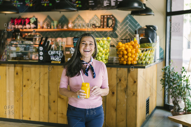 Cheerful mature woman holding mason jar with fresh juice while walking in cafe