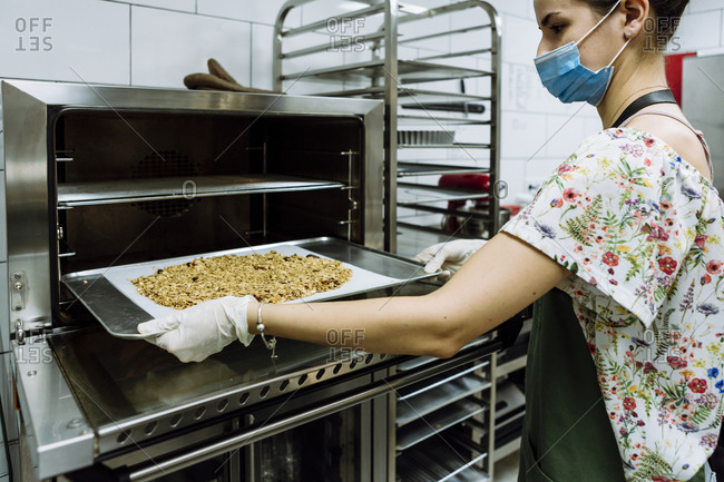 Young female baker positioning sheet in oven at bakery kitchen during pandemic