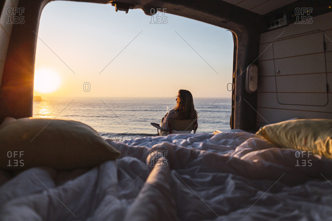 Woman admiring sunset view while  sitting on chair by camper van at beach
