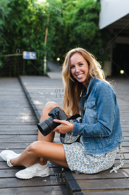 Smiling beautiful blond woman holding digital camera while sitting on footpath