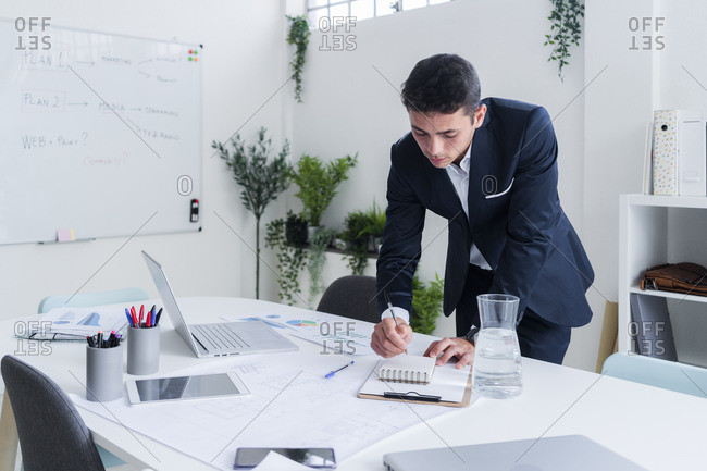 Handsome entrepreneur writing in diary while planning strategy at office desk