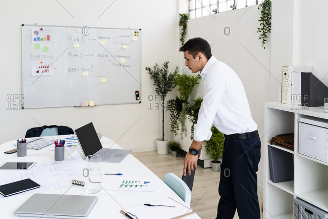 Male professional looking at laptop on desk while standing in creative office