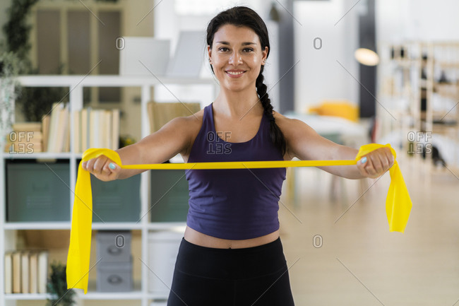 Smiling young fitness female stretching with resistance band standing at home