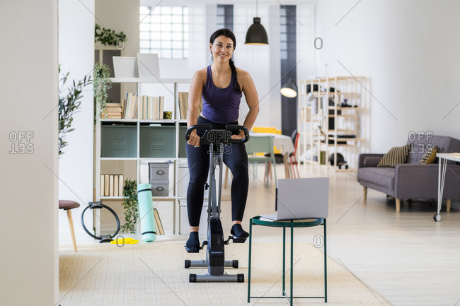 Smiling female athlete exercising on exercise bike while using laptop at home