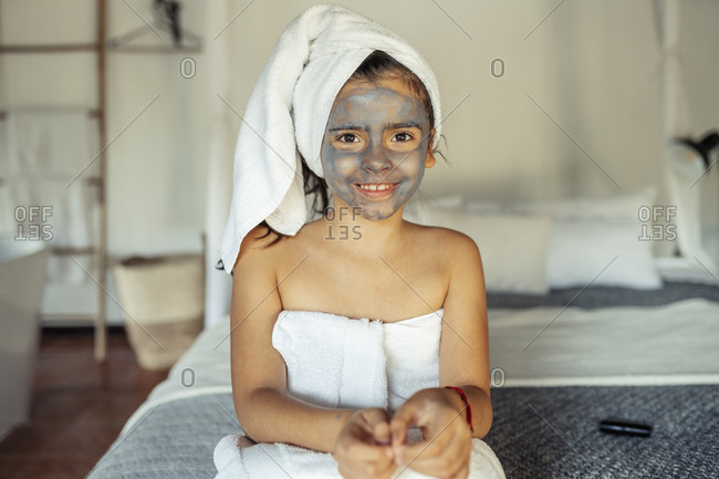Smiling girl covered in towel with facial mask on face sitting on bed at home