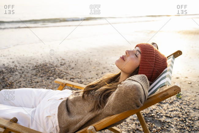 Young woman relaxing on folding chair with eyes closed at beach during sunset